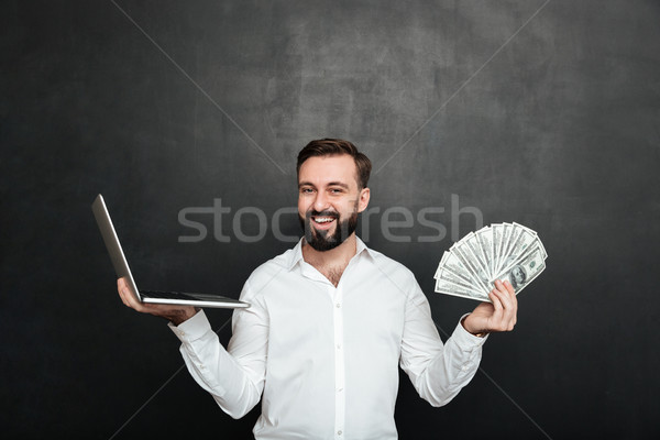 Portrait of cheerful rich man in white shirt winning lots of mon Stock photo © deandrobot
