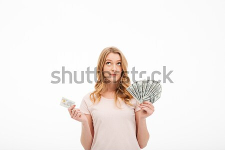 Thinking young lady holding money and credit card. Stock photo © deandrobot