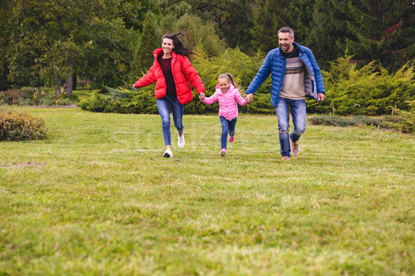 Young happy family of three spending fun time together Stock photo © deandrobot