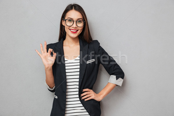 Smiling asian business woman in eyeglasses with arm on hip Stock photo © deandrobot