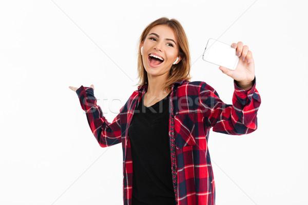 Boldog fiatal nő mobiltelefon fülhallgató kép áll Stock fotó © deandrobot