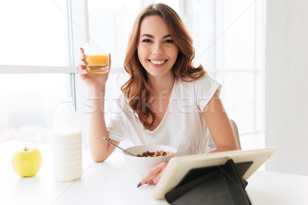 Signora seduta cucina bere succo immagine Foto d'archivio © deandrobot