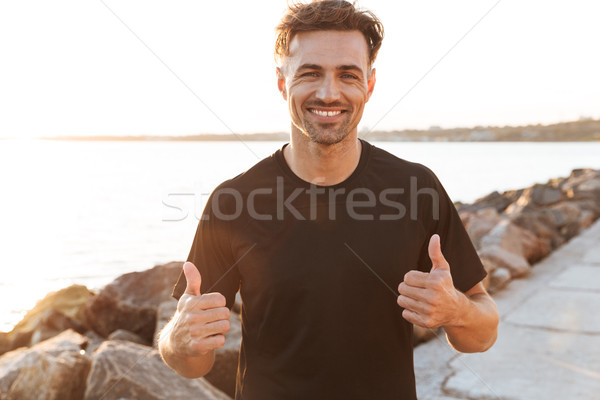 Portrait of a cheerful sportsman celebrating success Stock photo © deandrobot