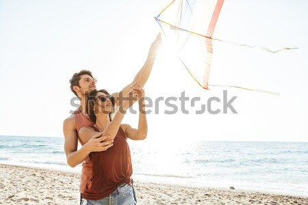 Cheerful young man carrying his girlfriend on his back Stock photo © deandrobot