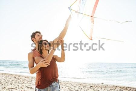 Derűs fiatalember hordoz barátnő hát sétál Stock fotó © deandrobot