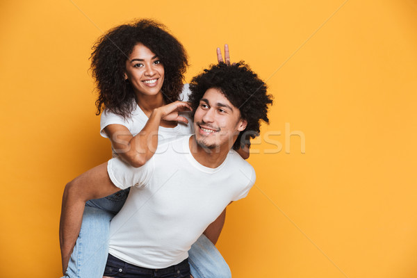 Portrait of a happy african man carrying girlfriend Stock photo © deandrobot