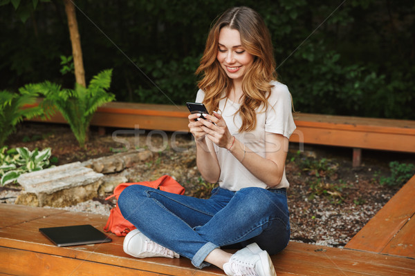 Stock photo: Smiling young girl using mobile phone