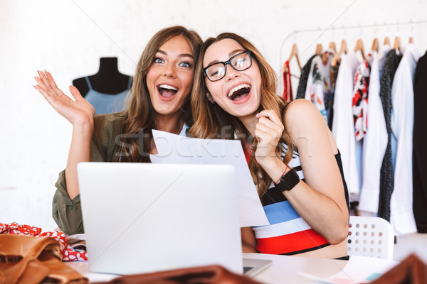 Two happy young women clothes designers working Stock photo © deandrobot