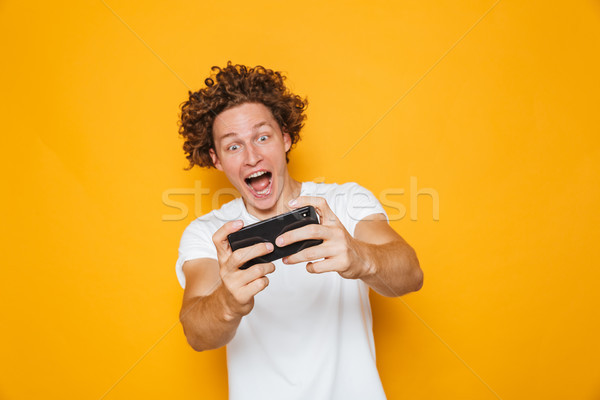 Cheerful excited guy in casual t-shirt playing online video game Stock photo © deandrobot