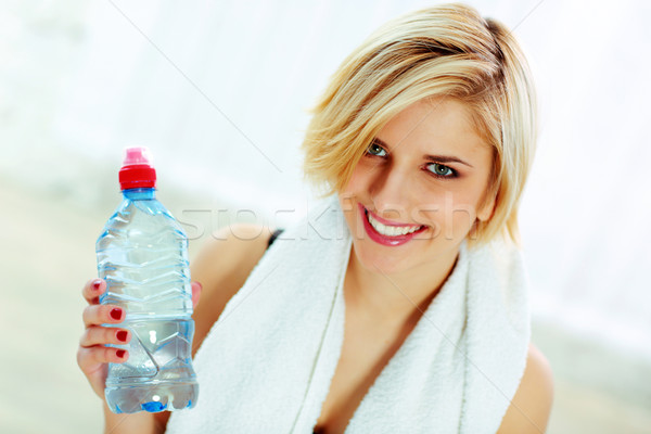 Closeup portrait of a young cheerful fit woman with bottle of water Stock photo © deandrobot