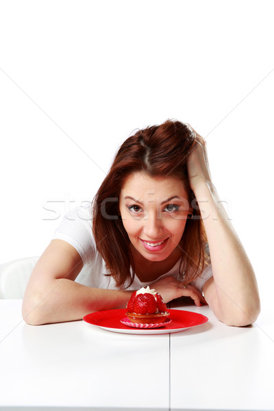 Smiling woman sitting at the table with fresh strawberry cake isolated on a white background Stock photo © deandrobot