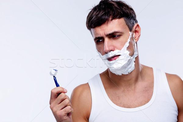 Portrait of a pensive man shaving over gray background Stock photo © deandrobot