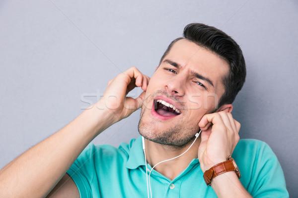 Genç şarkı söyleme kulaklık gri müzik mutlu Stok fotoğraf © deandrobot