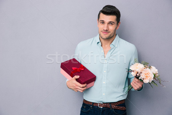 Young man holding gift box and flowers Stock photo © deandrobot