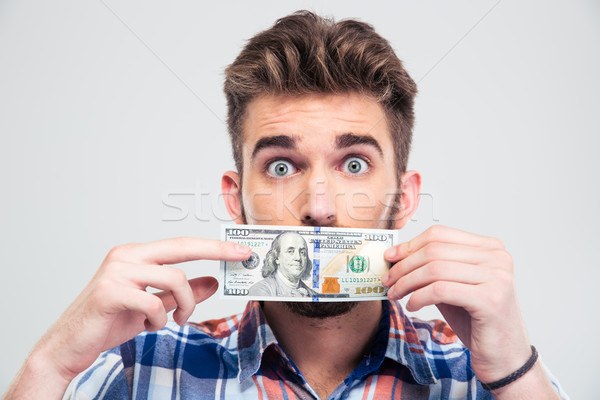 Man covering his mouth with bill of USA dollar Stock photo © deandrobot