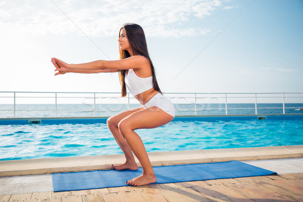 Girl working out on yoga mat  Stock photo © deandrobot