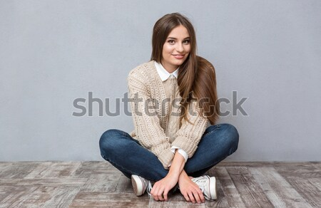 Boldog izgatott fiatal nő ül lábak keresztbe hosszú haj Stock fotó © deandrobot