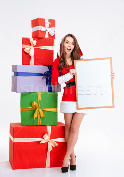 Stock photo: Cheerful woman in santa claus cloth holding blank board