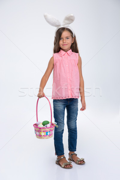 Little girl with rabbit ears holding basket of eggs Stock photo © deandrobot