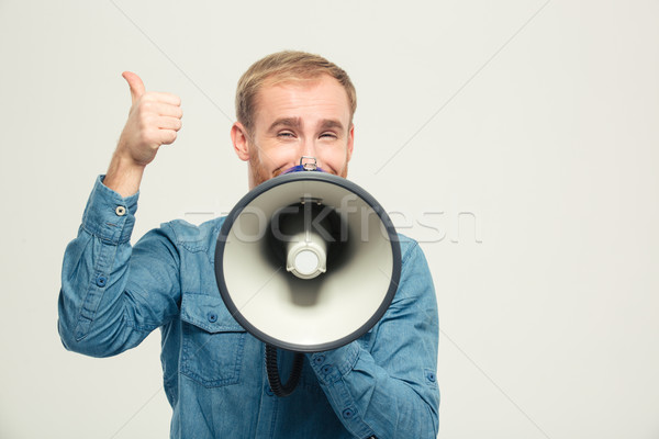 Happy man with megaphone showing thumb up Stock photo © deandrobot