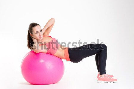 Pretty young fitness woman working out with fitball  Stock photo © deandrobot