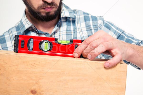 Close up of concenrated bearded young man using spirit level Stock photo © deandrobot
