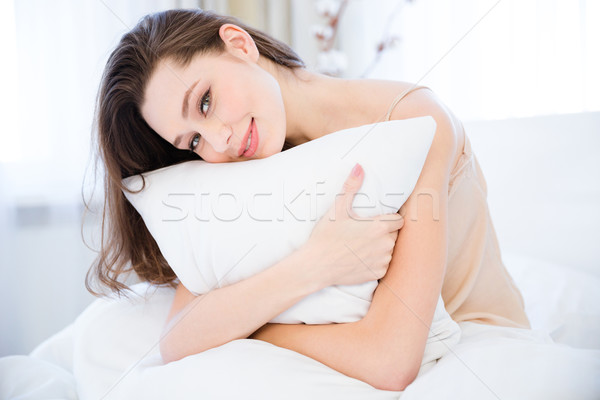 Happy relaxed young woman hugging pillow on bed Stock photo © deandrobot