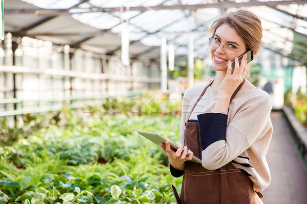 Smiling woman gardener using mobile phone and tablet in greenhouse Stock photo © deandrobot