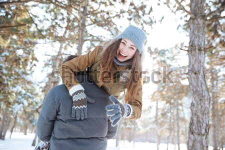 Amusing woman thowing snowball in her boyfriend face  Stock photo © deandrobot