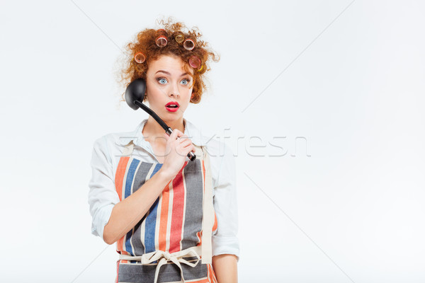 Amazed housewife in apron holding soup ladle Stock photo © deandrobot
