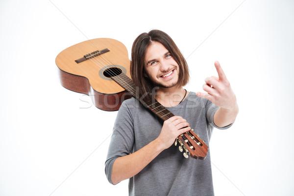 Derűs fiatalember tart gitár kő kézmozdulat Stock fotó © deandrobot