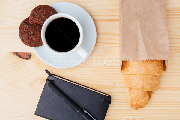Croissant, coffee and black notebook on wooden table Stock photo © deandrobot
