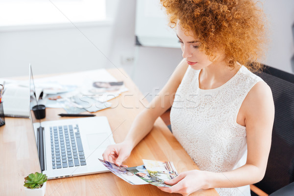 Woman photographer sitting on workplace and choosing photos Stock photo © deandrobot
