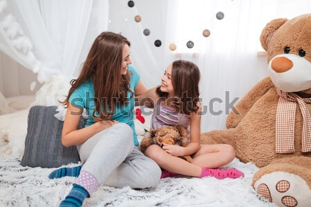 Top view of two cheerful charming sisters sitting and colouring  Stock photo © deandrobot