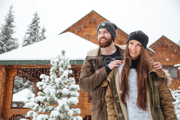 Couple standing near log cabin in snowy weather Stock photo © deandrobot