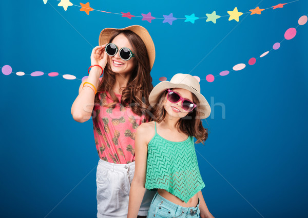 Two cheerful beautiful sisters in hats and sunglasses  Stock photo © deandrobot