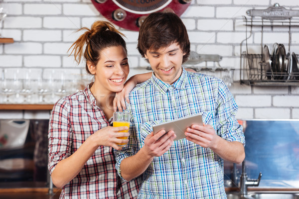 Stock photo: Happy couple drinking orange juice and using tablet on kitchen