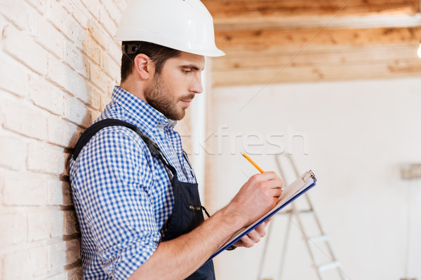 Builder standing backwards to the wall with clipboard Stock photo © deandrobot