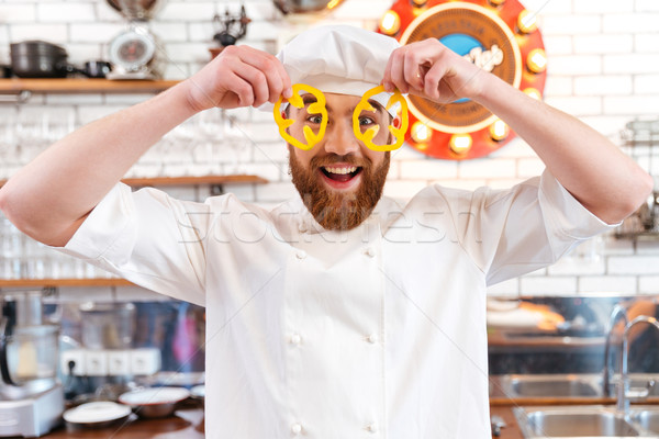 Funny chef cook looking through slices of yellow bell pepper Stock photo © deandrobot