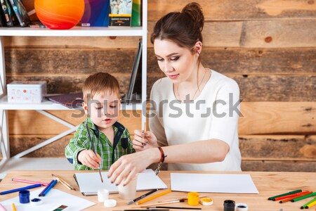 Mother touching face of son with hands painted in paints Stock photo © deandrobot