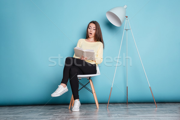 Shocked pretty girl looking at the book over blue background Stock photo © deandrobot