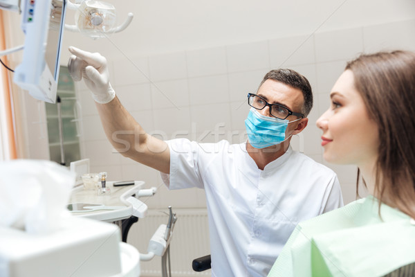 Dentist explaining x ray picture to patient on LED monitor Stock photo © deandrobot
