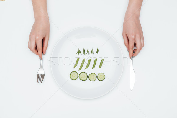 Woman eating cucumber, asparagus and rosemary on the plate Stock photo © deandrobot