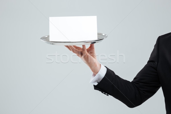 Hand of waiter in suit holding tray with blank card Stock photo © deandrobot