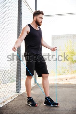 Mosolyog fitnessz férfi ül lábak keresztbe mutat Stock fotó © deandrobot