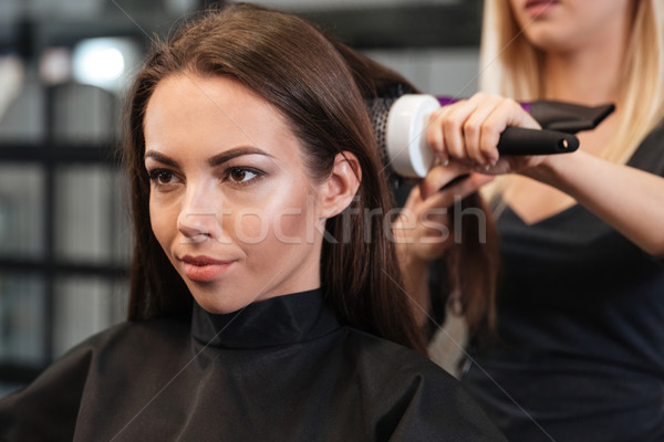 Close-up portrait of stylist drying woman hair in salon Stock photo © deandrobot