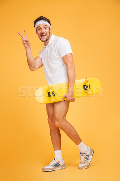 Young man holding a skateboard and showing v sign Stock photo © deandrobot
