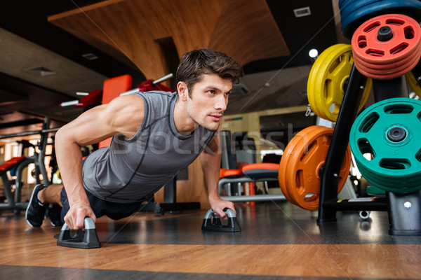 Fitness man working out and doing push-ups in gym Stock photo © deandrobot