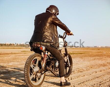 Fiatal brutális férfi vezetés motorkerékpár oldalnézet Stock fotó © deandrobot