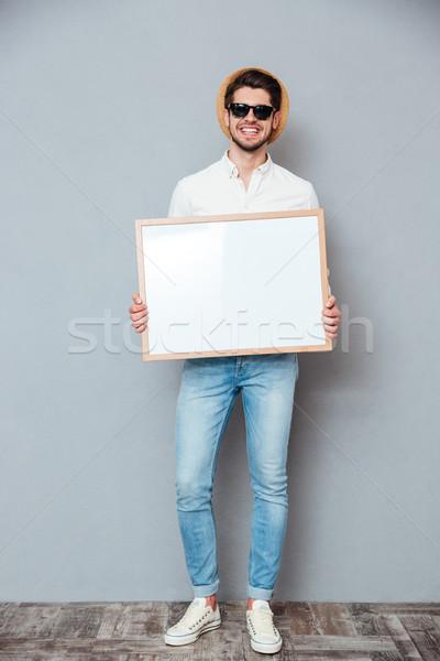 笑みを浮かべて 若い男 帽子 サングラス ホワイトボード ストックフォト © deandrobot